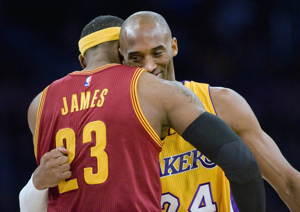 In this Jan. 15, 2015, file photo, Los Angeles Lakers guard Kobe Bryant, right, and Cleveland Cavaliers forward LeBron James hug before the start of an NBA basketball game, in Los Angeles. (Paul R ...