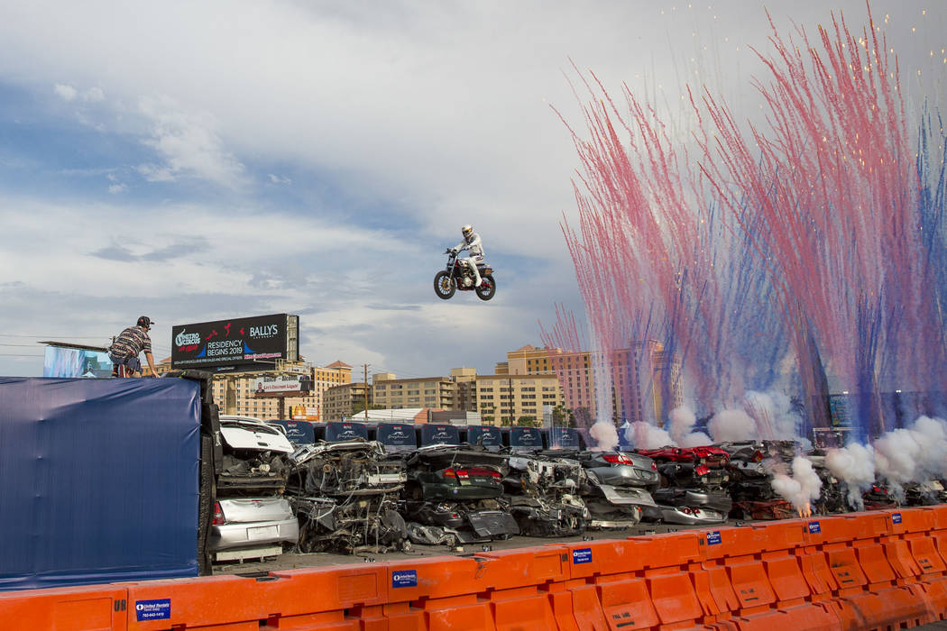 """Daredevil Travis Pastrana jumps over 52 crushed cars on an Indian Scout FTR750 motorcycle during """"Evel Live,"""" a three-hour live tribute show to stuntman Evel Knievel, in a lot behind Pla ..."""