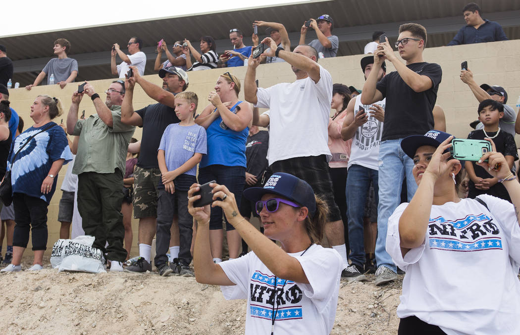 Attendees pull out their phones to capture Travis Pastrana jump over 52 crushed cars on an Indian Scout FTR750 motorcycle at the Evel Live event where Travis Pastrana attempted to exceed three of ...
