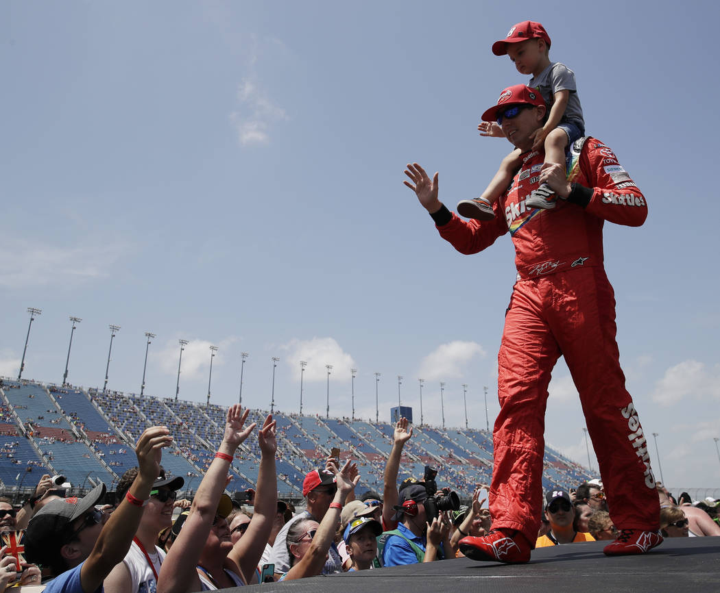 Kyle Busch and his son Brexton Busch, greet fans before a NASCAR Cup Series auto race at Chicagoland Speedway in Joliet, Ill., Sunday, July 1, 2018. (AP Photo/Nam Y. Huh)