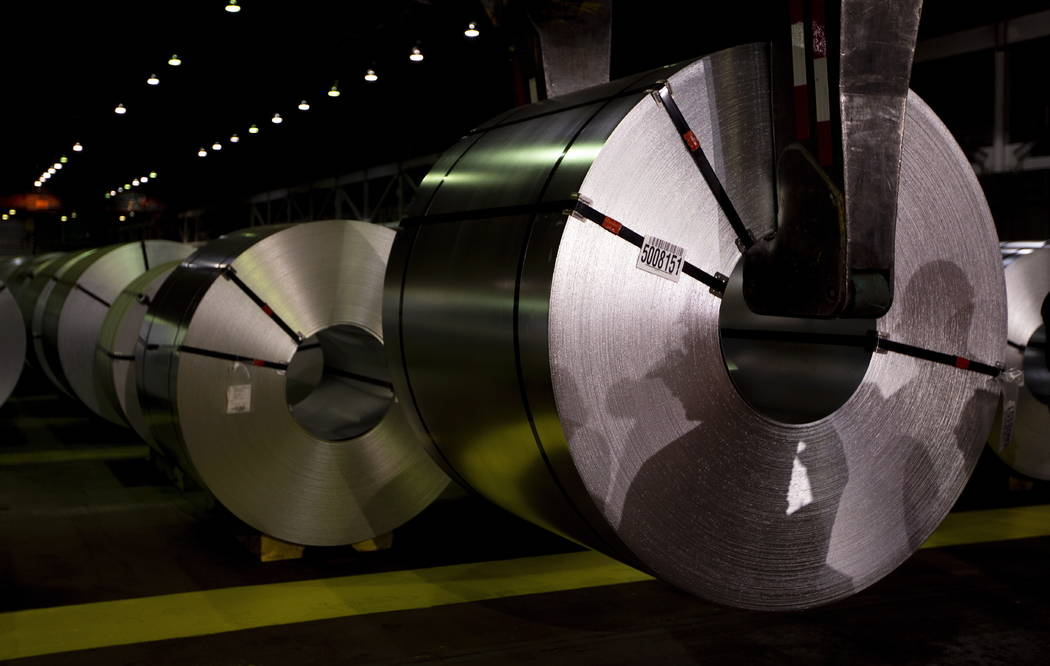 FILE - In this June 29, 2018, file photo, shadows of workers are cast on rolls of coated steal at Stelco in Hamilton, Ontario. Canada has begun imposing tariffs on $12.6 billion in U.S. goods as r ...