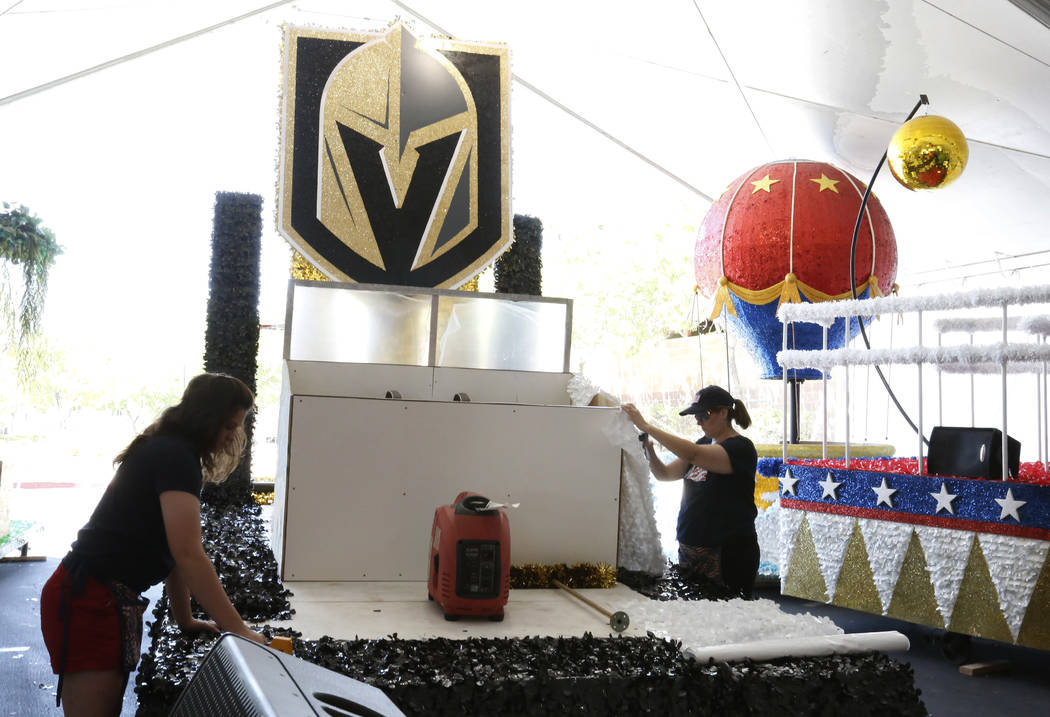 Stephanie Day, a volunteer, left, and Kelley Cawood, communications coordinator for the Summerlin Council, decorate the Vegas Knights float, to be featured in the Summerlin Patriotic Parade, at th ...