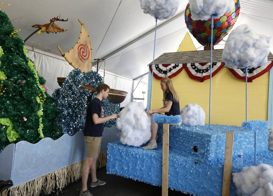 Cole Willson, and Katie Condron, both volunteers, decorate the Pixar film ''Up'' themed float, to be featured in the Summerlin Patriotic Parade, at the Trails Park on Monday, July 02, 2018, in Su ...