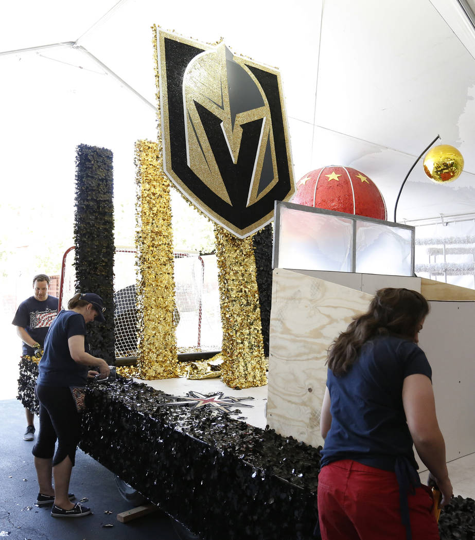 Julien Mihy, left, a volunteer, Kelley Cawood, communications coordinator for the Summerlin Council, center, and Stephanie Day, a volunteer, right, decorate the Vegas Knights float, to be featured ...