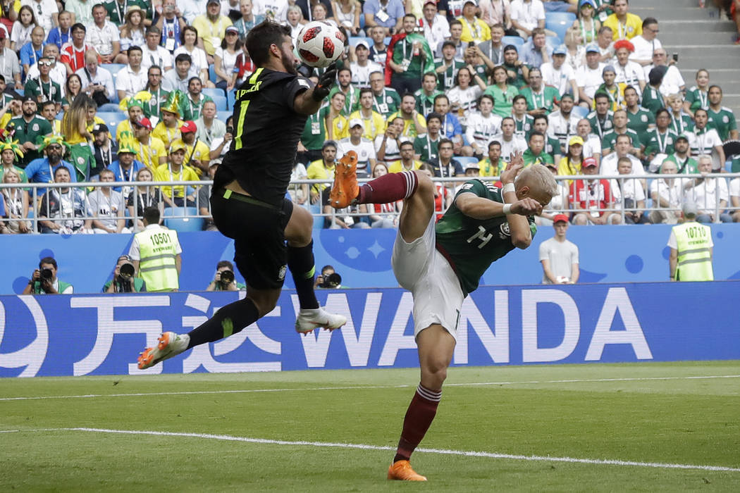 Brazil goalkeeper Alisson, left, blocks a kick by Mexico's Javier Hernandez, right, during the round of 16 match between Brazil and Mexico at the 2018 soccer World Cup in the Samara Arena, in Sama ...
