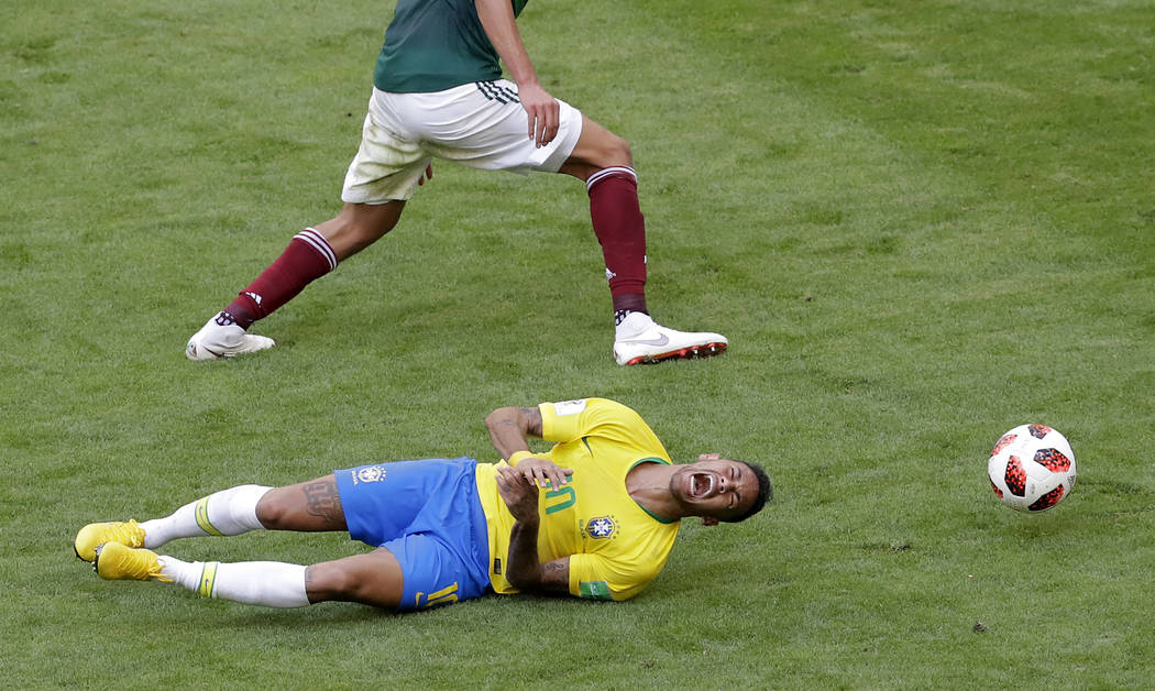 Brazil's Neymar, bottom, challenges for the ball with Mexico's Edson Alvarez during the round of 16 match between Brazil and Mexico at the 2018 soccer World Cup in the Samara Arena, in Samara, Rus ...