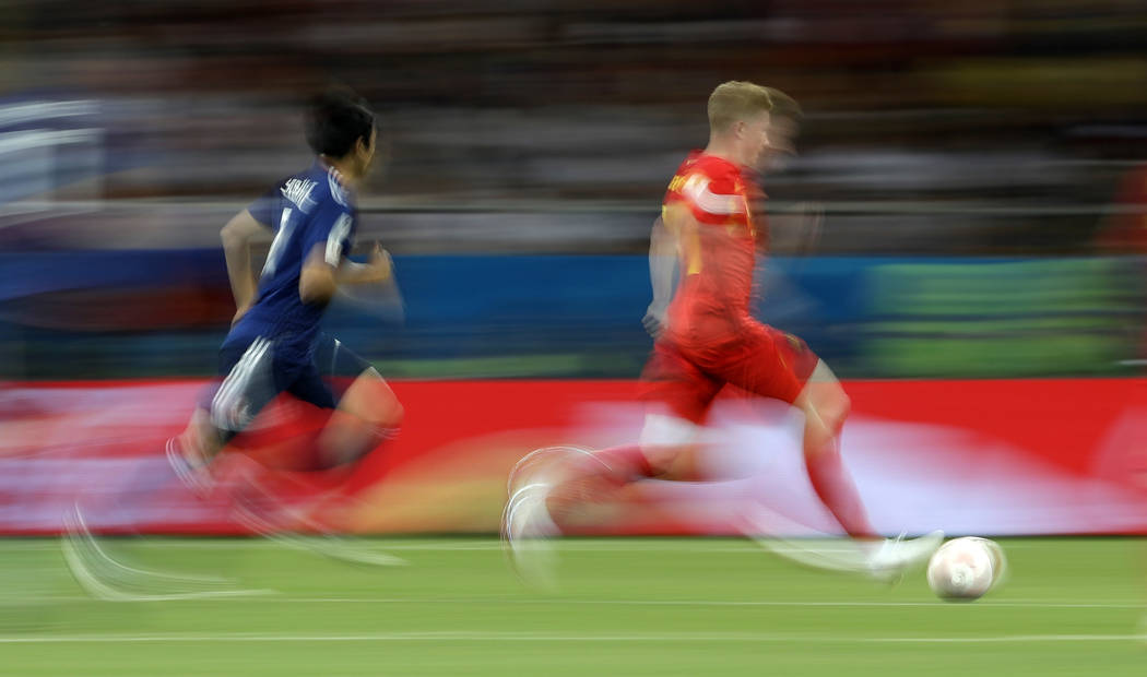 Belgium's Kevin De Bruyne, right, runs for the ball in this slow shutter speed photo during the round of 16 match between Belgium and Japan at the 2018 soccer World Cup in the Rostov Arena, in Ros ...