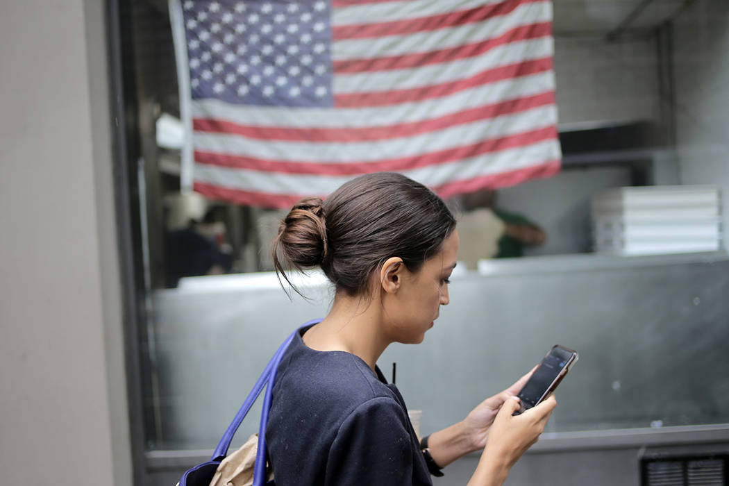 Alexandria Ocasio-Cortez checks her phone while walking to her next appointment in New York, Wednesday, June 27, 2018. The 28-year-old political newcomer who upset U.S. Rep. Joe Crowley in New Yor ...