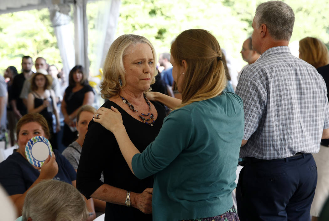 Judy Hiaasen, left, sister of Rob Hiaasen, one of the journalists killed in the shooting at The Capital Gazette newspaper offices, speaks with a mourner during a memorial service, Monday, July 2, ...