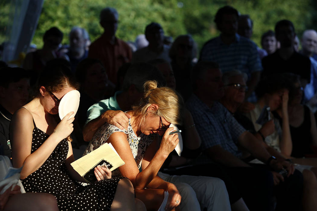 Maria Hiaasen, second from left, widow of Rob Hiaasen, and her daughter Sam, left, react during a memorial service for Rob Hiaasen, one of the journalists killed in the shooting at the Capital Gaz ...