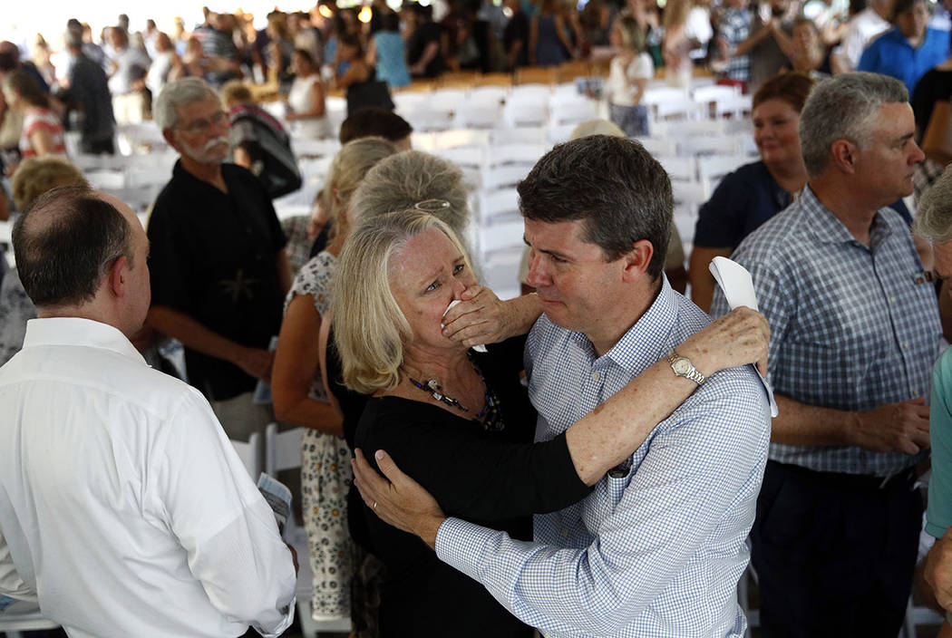 Judy Hiaasen, center left, sister of Rob Hiaasen, one of the journalists killed in the shooting at The Capital Gazette newspaper offices, hugs her nephew Scott following a memorial service, Monday ...