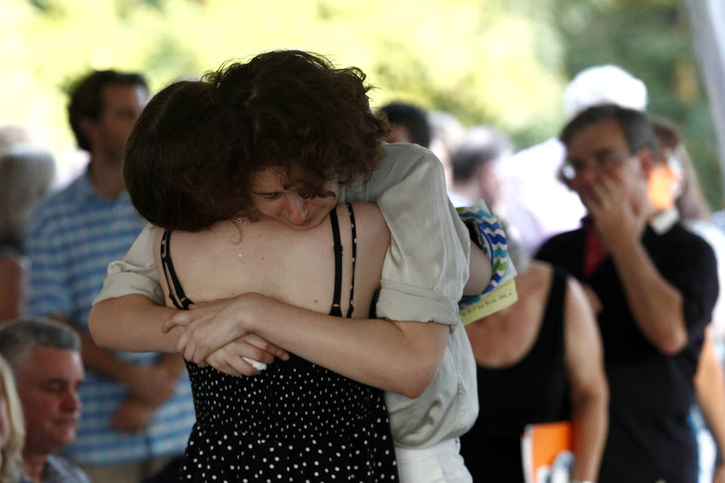 Hannah Hiaasen, center right, hugs her sister Sam following a memorial service for their father, Rob Hiaasen, one of the journalists killed in the shooting at The Capital Gazette newspaper offices ...