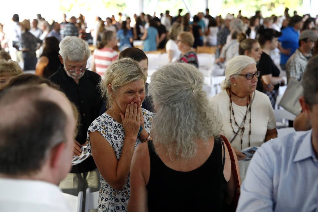 Maria Hiaasen, center left, widow of Rob Hiaasen, reacts following a memorial service for her late husband, one of the journalists killed in the shooting at the Capital Gazette newspaper offices, ...