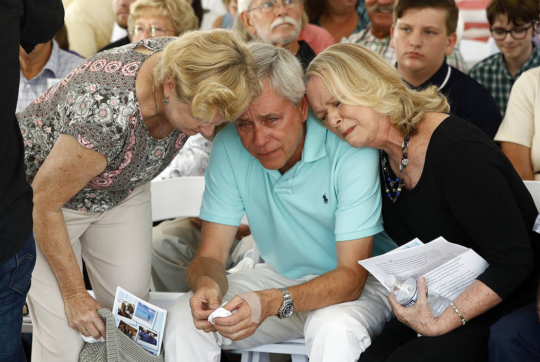 Carl Hiaasen, center, brother of Rob Hiaasen, one of the journalists killed in the shooting at The Capital Gazette newspaper offices, is consoled by his sister Judy, right, and Rob Hiaasen's widow ...