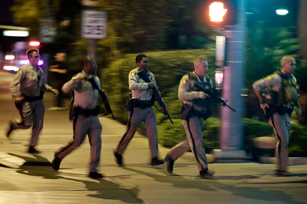 Las Vegas police run toward the scene of a mass shooting near Mandalay Bay on the Las Vegas Strip on Oct. 1, 2017. (John Locher/AP)