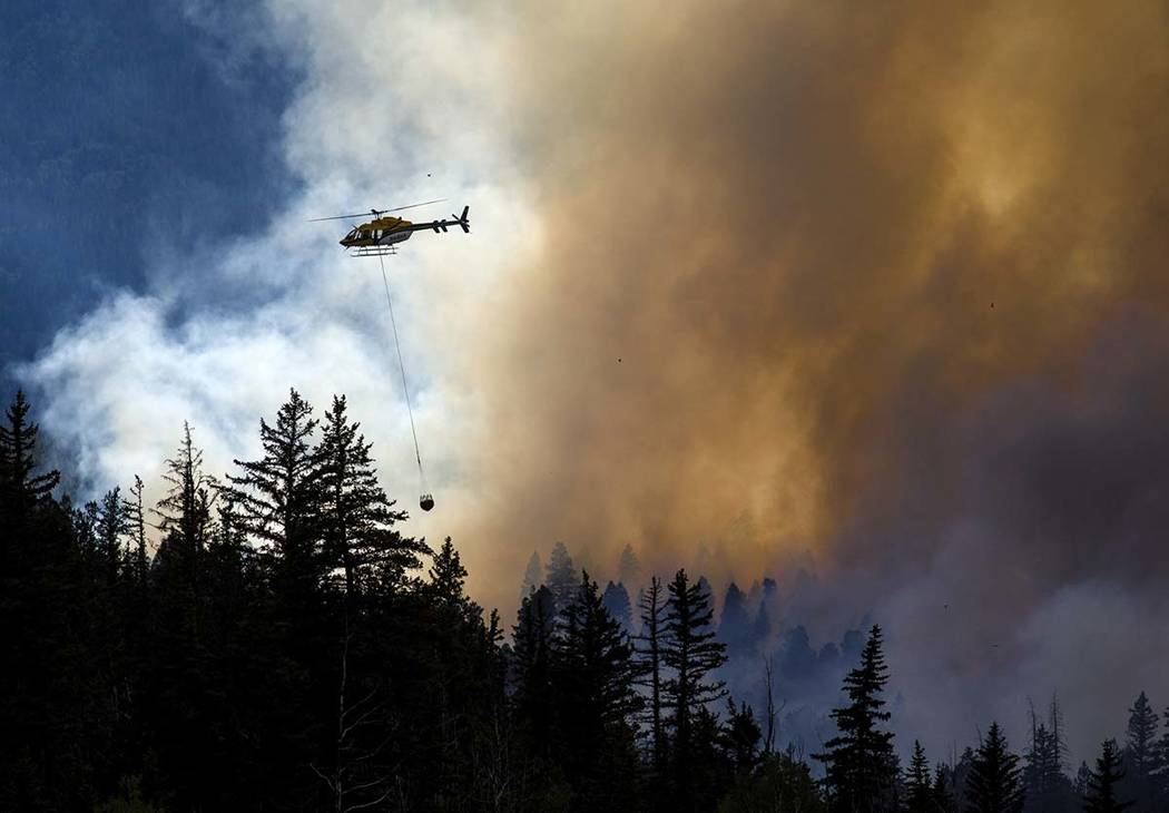 A helicopter transports water to contain the Weston Pass Fire, Monday, July 2, 2018, near Fairplay, Colo. In Colorado, more than 2,500 homes were under evacuation orders as firefighters battled mo ...
