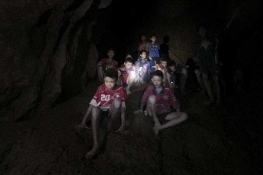 This Monday, July 2, 2018, photo released by Tham Luang Rescue Operation Center, shows the boys and their soccer coach as they were found in a partially flooded cave, in Mae Sai, Chiang Rai, Thail ...