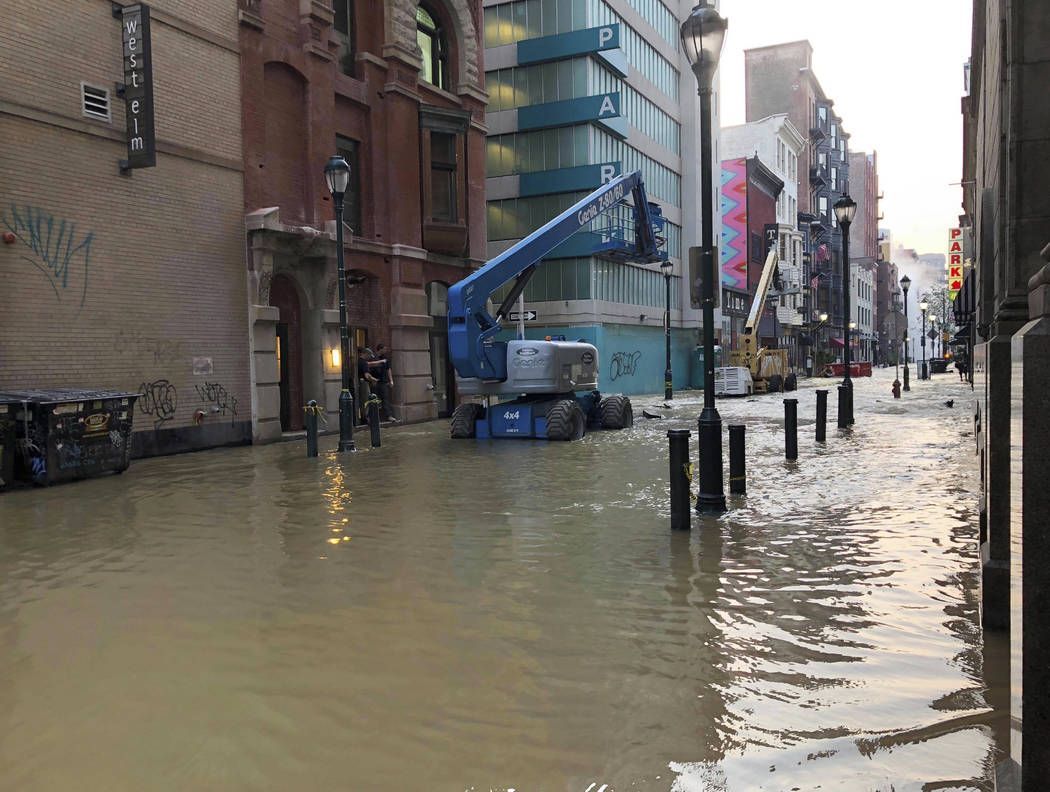 Water covers a street after a water main broke in Philadelphia on Tuesday morning July 3, 2018. The break happened before 4 a.m. Tuesday, and a number of center city streets have been closed. (Pat ...