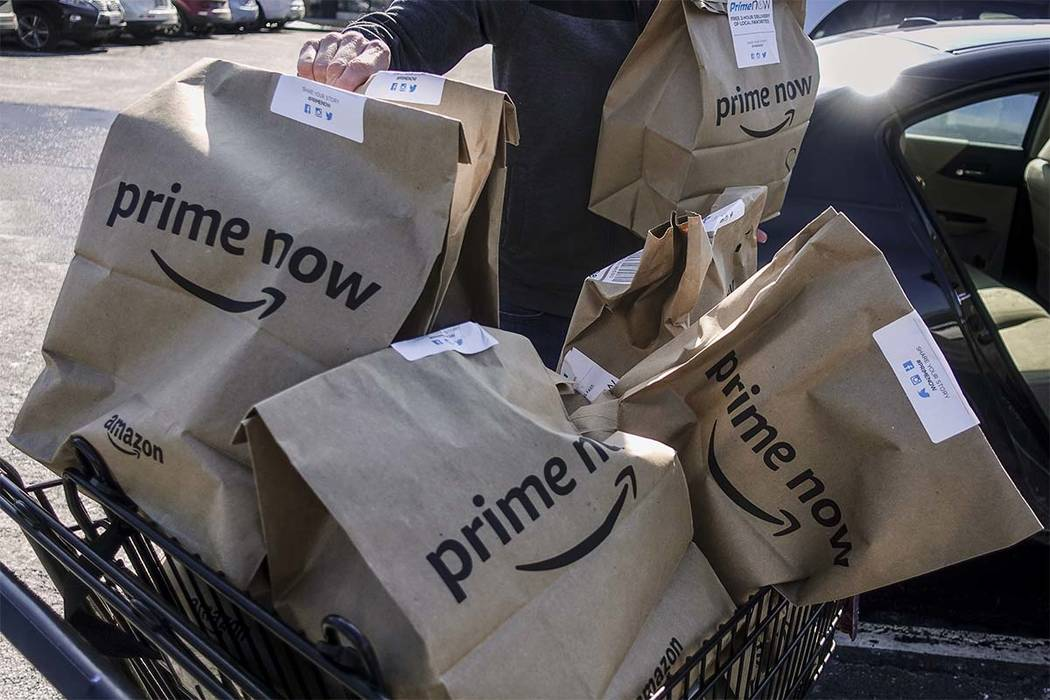 In this Feb. 8, 2018, file photo, Amazon Prime Now bags full of groceries are loaded for delivery by a part-time worker outside a Whole Foods store in Cincinnati. Amazon's Prime Day deals are co ...