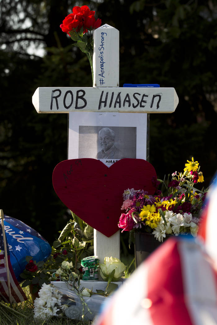A cross with the name of editor Robert Hiaasen is placed at a makeshift memorial outside the office building housing The Capital Gazette newspaper in Annapolis, Md., on Sunday, July 1, 2018. Prose ...