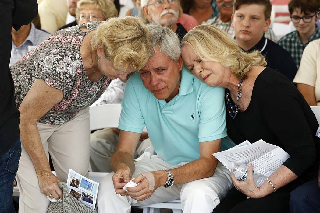 Carl Hiaasen, center, brother of Rob Hiaasen, one of the journalists killed in the shooting at The Capital Gazette newspaper offices, is consoled by his sisters Barb, left, and Judy during a memor ...