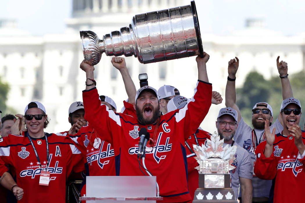 In this Tuesday, June 12, 2018 file photo Washington Capitals Alex Ovechkin, from Russia, holds up the Stanley Cup trophy during the NHL hockey team's Stanley Cup victory celebration, at the Natio ...