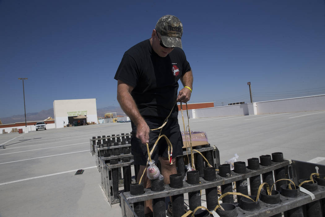 Tom Williams, pyrotechnician with Fireworks by Grucci, drops one of over 700 shells inside a tube in preparation for a Fourth of July firework show at the Fiesta Rancho casino-hotel in Las Vegas, ...