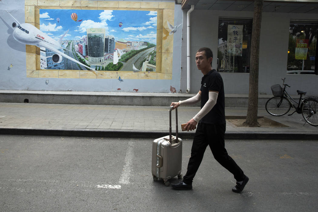 A man pushes a piece of luggage past a mural depicting air travel and a prosperous city in Beijing, China, Tuesday, July 3, 2018. Barring a last-minute breakthrough, the Trump administration on Fr ...