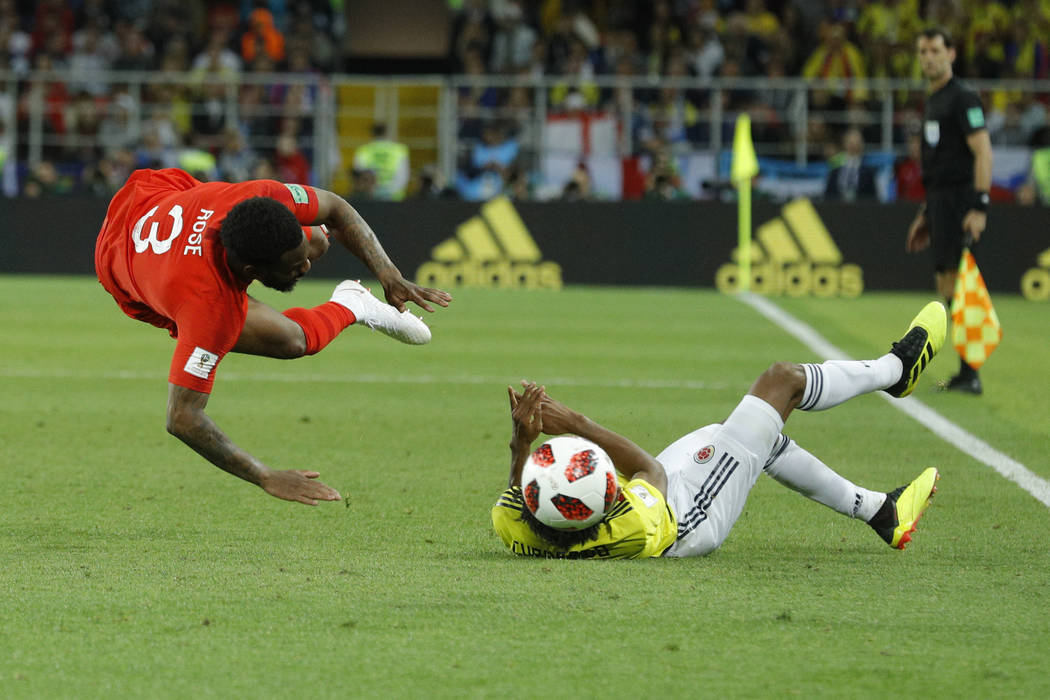 Colombia's Juan Cuadrado, right, fouls England's Danny Rose during the round of 16 match between Colombia and England at the 2018 soccer World Cup in the Spartak Stadium, in Moscow, Russia, Tuesda ...