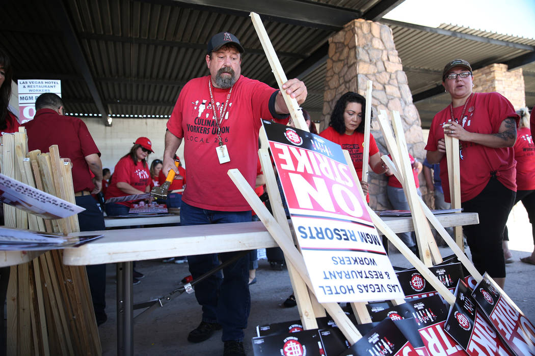 "Culinary Union organizer Mark Noonkester makes strike picket signs at the newly opened ""Strike HQ"" at the intersection of Wyoming Avenue and Fairfield Avenue in Las Vegas, Friday, Ju ..."