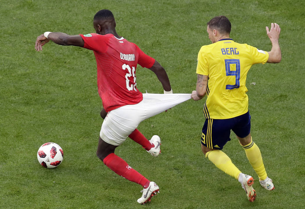 Switzerland's Johan Djourou, left, duels for the ball with Sweden's Marcus Berg during the round of 16 match between Switzerland and Sweden at the 2018 soccer World Cup in the St. Petersburg Stadi ...