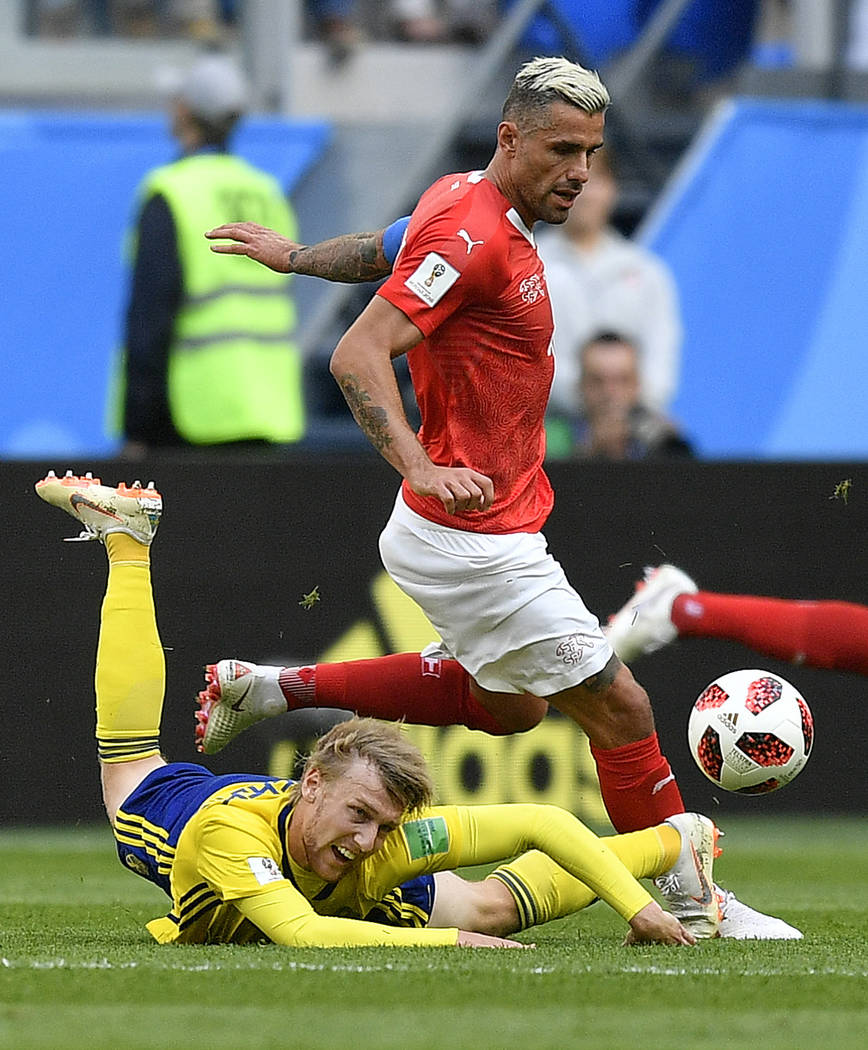 Switzerland's Valon Behrami, rear, and Sweden's Emil Forsberg challenge for the ball during the round of 16 match between Switzerland and Sweden at the 2018 soccer World Cup in the St. Petersburg ...
