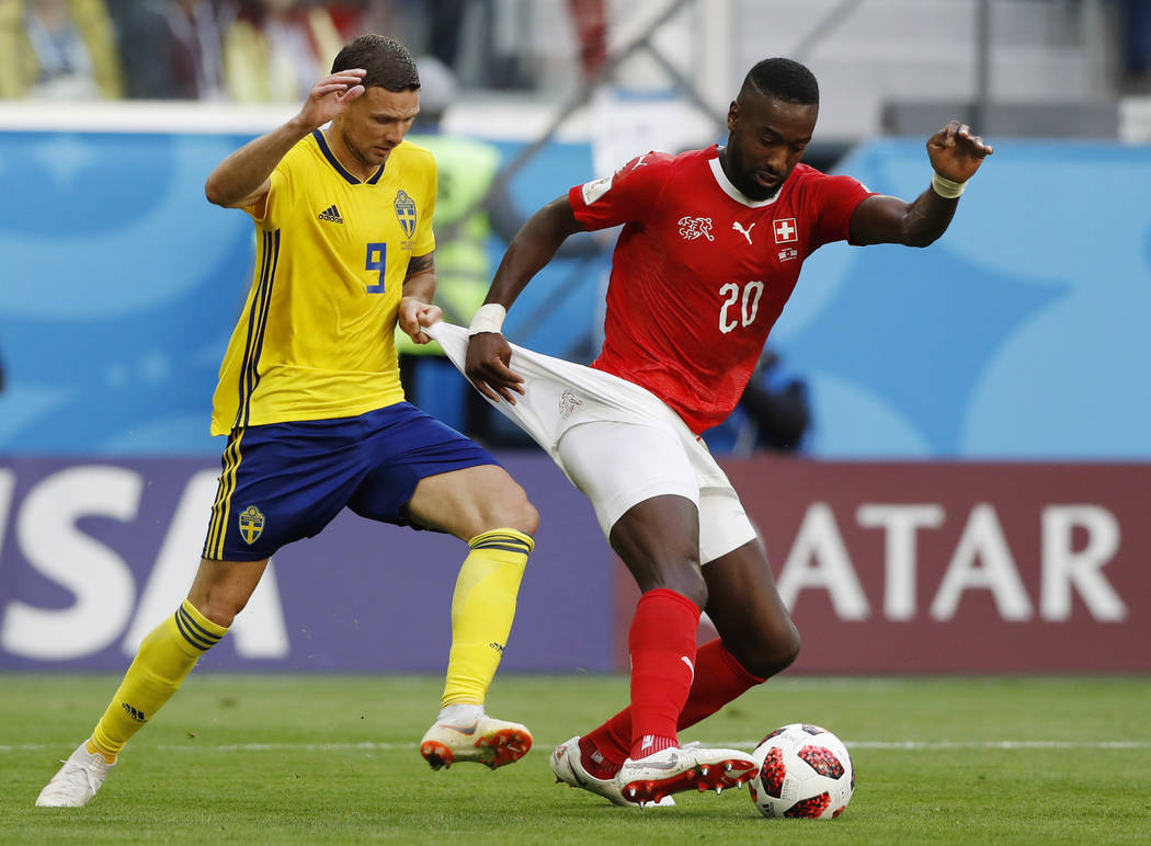 Sweden's Marcus Berg, left, battles for the ball with Switzerland's Johan Djourou during the round of 16 match between Switzerland and Sweden at the 2018 soccer World Cup in the St. Petersburg Sta ...