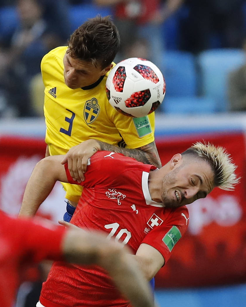 Sweden's Victor Lindelof, left, heads for the ball with Switzerland's Granit Xhaka during the round of 16 match between Switzerland and Sweden at the 2018 soccer World Cup in the St. Petersburg St ...