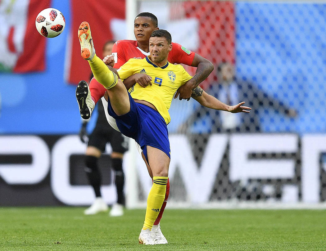 Switzerland's Manuel Akanji, rear, and Sweden's Marcus Berg challenge for the ball during the round of 16 match between Switzerland and Sweden at the 2018 soccer World Cup in the St. Petersburg St ...