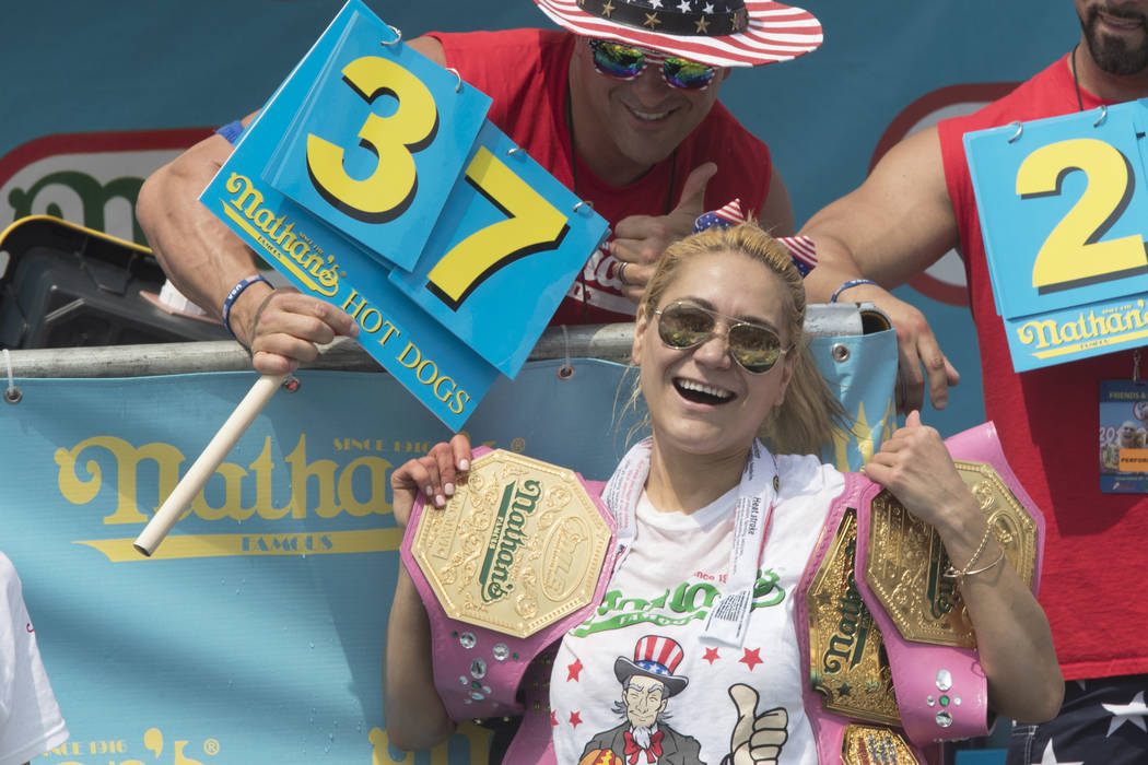 Reigning champion Miki Sudo celebrates after winning the women's competition of the Nathan's Famous Fourth of July hot dog eating contest, Wednesday, July 4, 2018, in New York's Coney Island. (AP ...