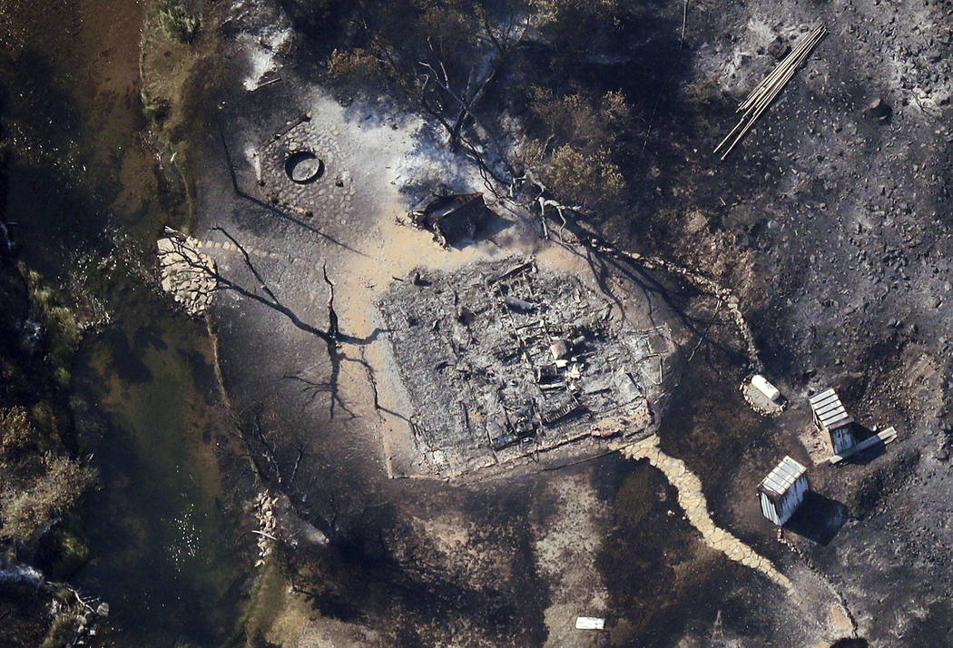 In this aerial photo, a burnt out structure is visible through the smoke as a wildfire continues to burn east of Strawberry Reservoir, in Wasatch County, Utah, Tuesday, July 3, 2018. The Utah fire ...