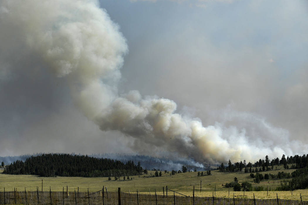In this Monday, July 2, 2018, photo, a large plume of smoke begins to build in the afternoon from a wildfire near Fairplay, Colo. The fire is burning about 20 miles south of Fairplay. (Helen H. Ri ...
