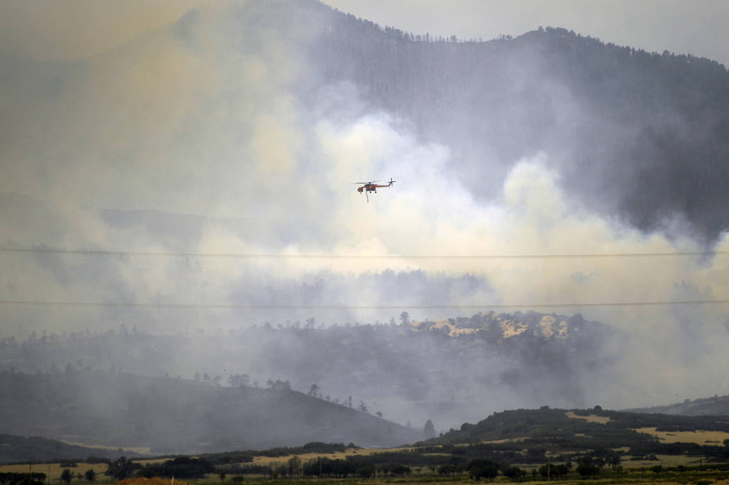 A helicopter moves along ridges to make water drops on the Spring Fire as it continues to burn in Costilla County Tuesday, July 3, 2018 near La Veta, Colo. While investigators believe it was start ...