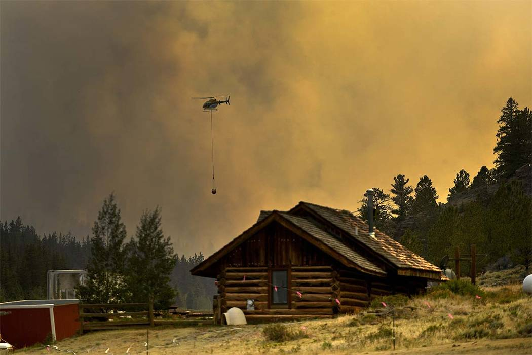 In this Monday, July 2, 2018 photo, a helicopter returns for water after making a water drop on a wildfire near Fairplay, Colo. The fire is burning about 20 miles south of Fairplay. Because of th ...