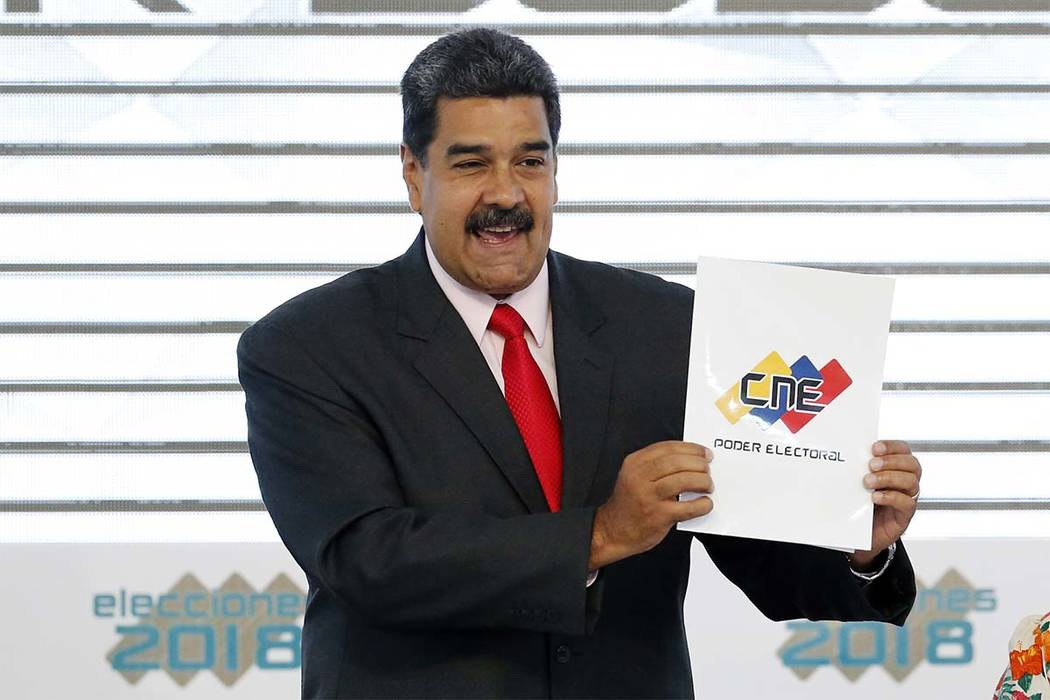 In this May 22, 2018, file photo, Venezuela's President Nicolas Maduro holds up the National Electoral Council certificate declaring him the winner of the presidential election, during a ceremony ...