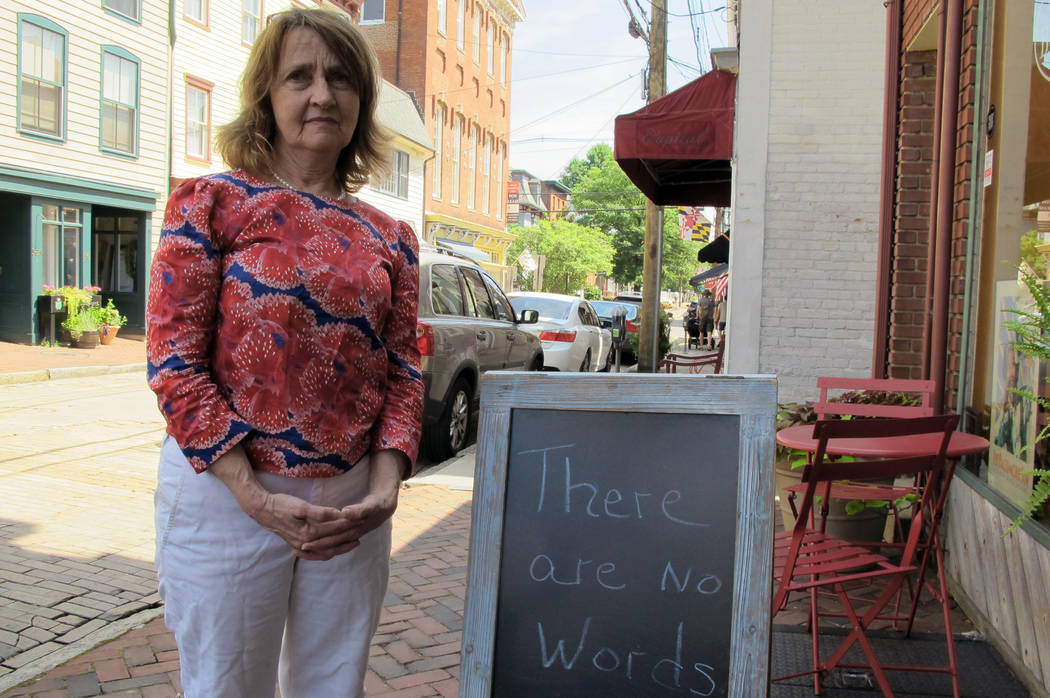 Mary Adams, owner of The Annapolis Bookstore, stands by a sign outside her store on Saturday, June 30, 2018 in downtown Annapolis, Md. Adams, who knew two of the journalists who were killed in the ...