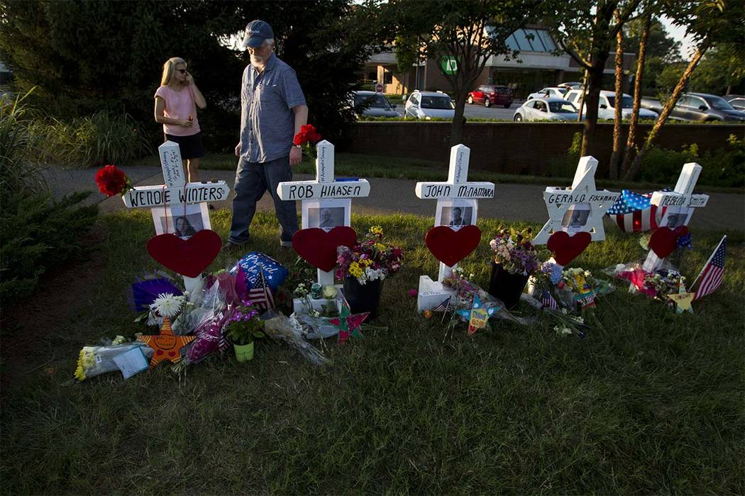 Capital Gazette reporter E.B. Furgurson III looks at the crosses representing his five colleagues at a makeshift memorial at the scene outside the office building housing The Capital Gazette newsp ...