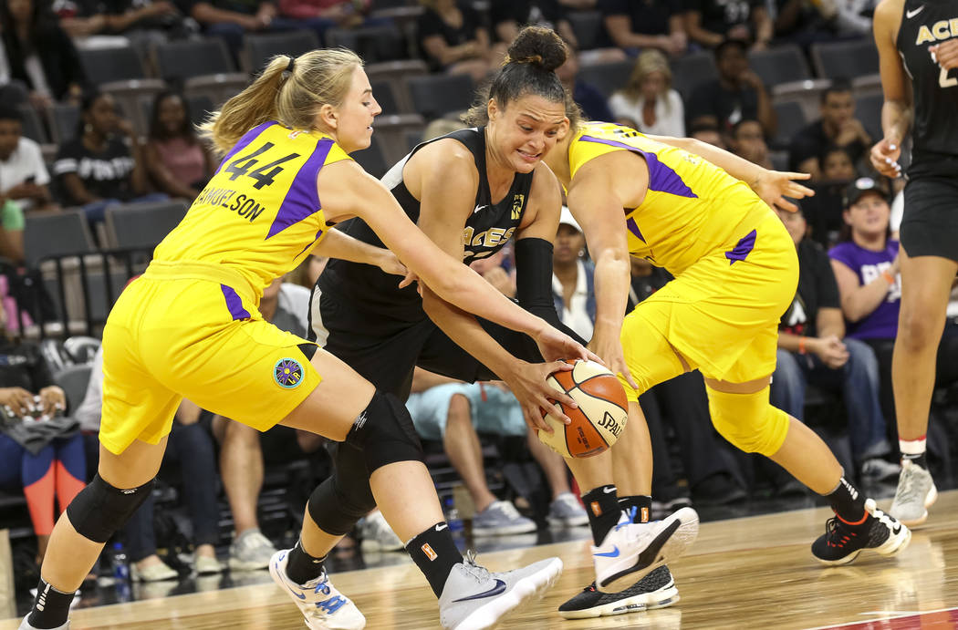 Las Vegas Aces guard Kayla McBride (21), center, attempts to drive the ball through Los Angeles Sparks forward Karlie Samuelson (44) and Sparks center Maria Vadeeva (10) during the second half of ...