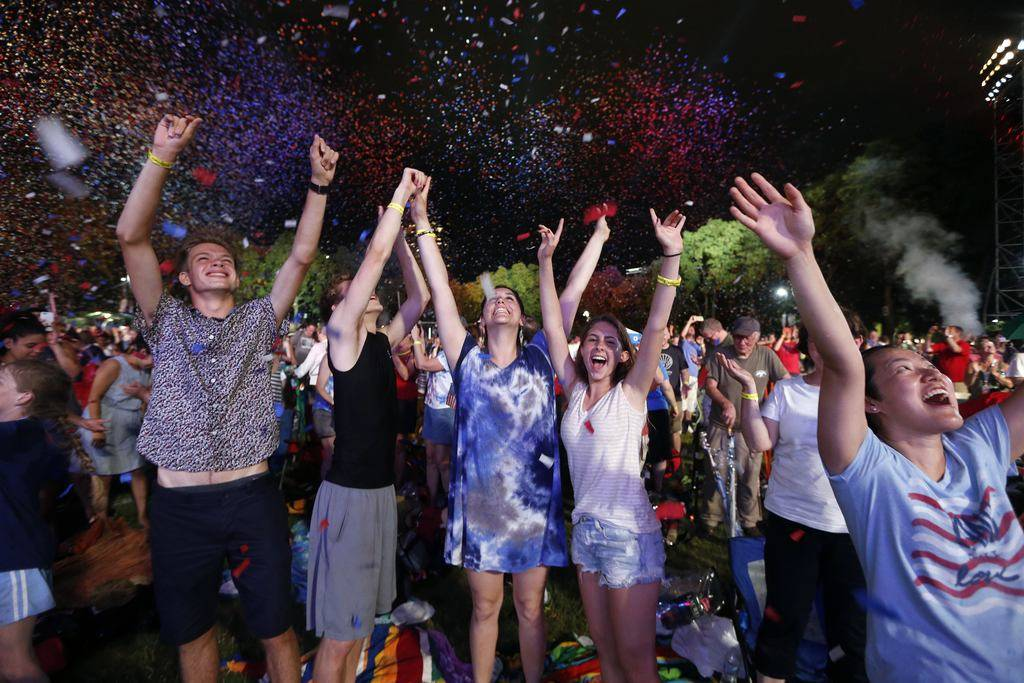 Spectators cheer as confetti falls during rehearsal for the Boston Pops Fireworks Spectacular in Boston, Tuesday, July 3, 2018. (AP Photo/Michael Dwyer)