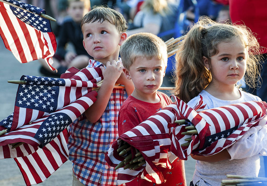 Brayden Austin, left, Gavin Colby, middle, and Brylee Roberge patiently wait with an armful of flags to be burned at Veterans Memorial Park in Lewiston, Maine, Tuesday, July 3, 2018, during the Sa ...