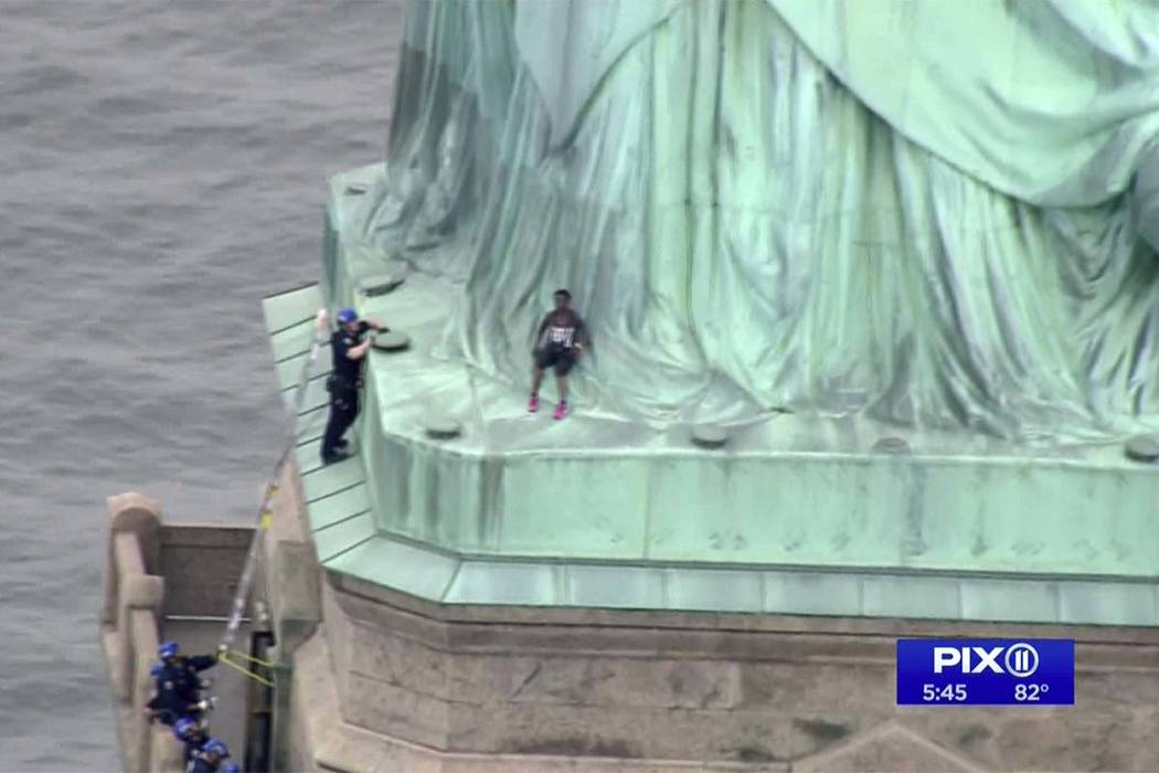 In this image made from video, a protester leans against the robes of the Statue of Liberty on Liberty Island, as a police officer tried to convince the woman to come down. (PIX11 via AP)