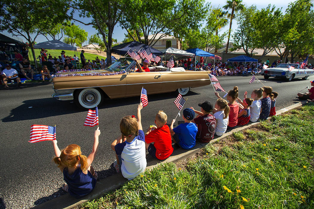 Children line the streets of Summerlin and wave to a parade entry. (Summerlin Council – Studio J, Eric Jamison)