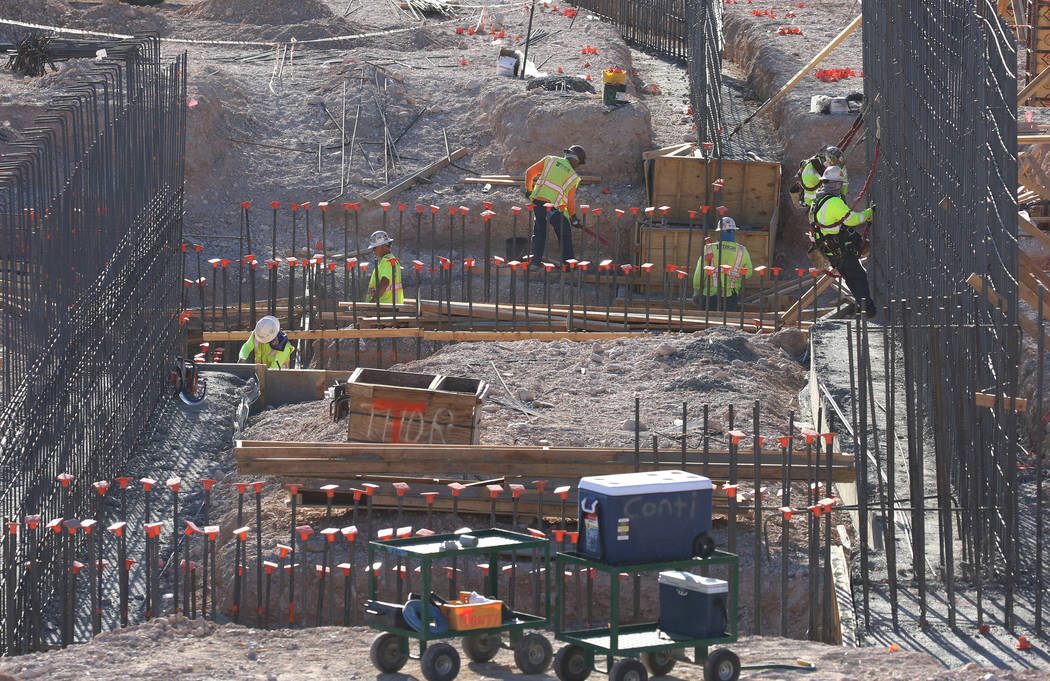 Construction workers, right, are tying rebar to make a newly constructed footing frame at the construction site of the new Las Vegas ballpark on Thursday, June 7, 2018, in Summerlin. Bizuayehu Tes ...