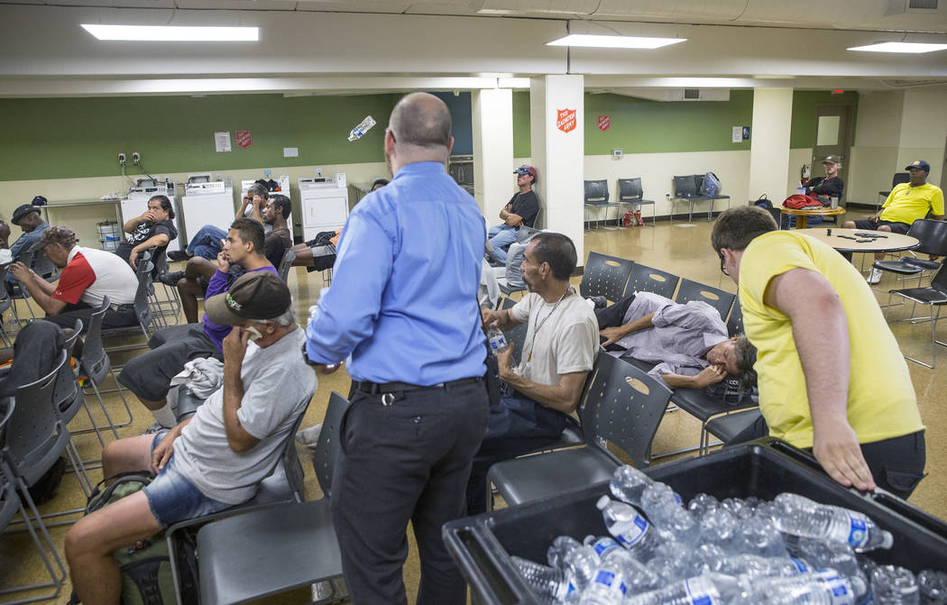 Shelter monitor Boston Brimhall, right, and homeless services coordinator Ryan McDonald hand out water at a cooling station at The Salvation Army on Thursday, July 5, 2018, in Las Vegas. Benjamin ...